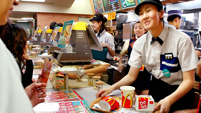 Sales clerks of fast food chain McDonald's serve meals to customers at a Tokyo shop. (AFP Photo / Yoshikazu Tsuno)