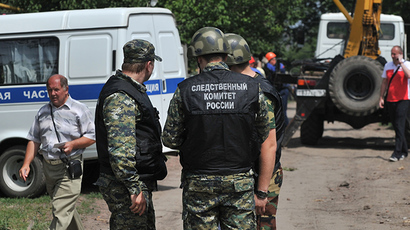 FILE photo. Law enforcement officers near a house in the town of Donetsk, Rostov-on-Don Region, whose territory was hit with one of high-explosive shells fired at the town from the Ukrainian territory on July 13, 2014. (RIA Novosti / Sergey Pivovarov)