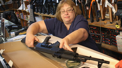 Cindy Sparr boxes up an AK-47 style rifle after selling it at Freddie Bear Sports sporting goods store. (AFP Photo / Getty Images / Scott Olson)