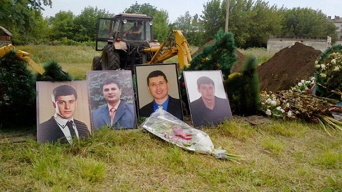 An excavator digs a hole by portraits of four missing Slavyansk residents, to exhume four unidentified bodies at a mass grave in the eastern Ukrainian city of Slavyansk on July 24, 2014. (AFP Photo / Marion Thibaut)