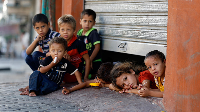 Displaced Palestinian children peak from under a shop door, where their family is taking shelter in Gaza City on July 26, 2014. (AFP Photo / Mohammed Abed)