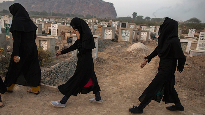 ARCHIVE PHOTO: Ahamdi women walk past graves at the Ahmadi graveyard in the town of Rabwa December 9, 2013 (Reuters / Zohra Bensemra)