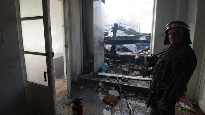 A firefighter in the Donetskoblenergo power company office building damaged during a rocket and mortar attack on Gorlovka, Donetsk region. (RIA Novosti / Mikhail Voskresenskiy)