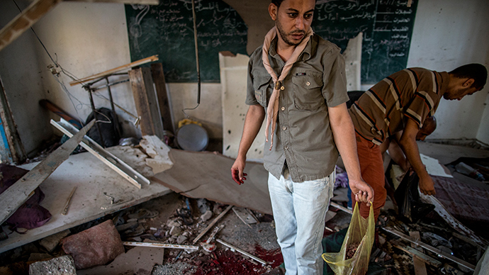 Palestinians collect human remains from a classroom inside a UN school in the Jabalia refugee camp after the area was hit by shelling on July 30, 2014 (AFP Photo / Marco Longari)