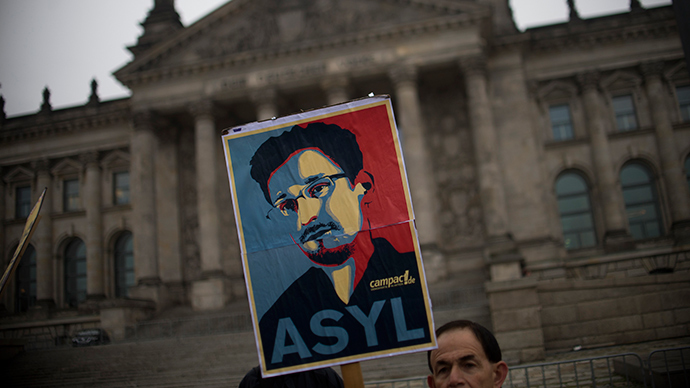 Campact activists hold up a portrait of US whistleblower Edward Snowden in front of the Reichstag building housing the Bundestag (lower house of parliament) in Berlin (AFP Photo)