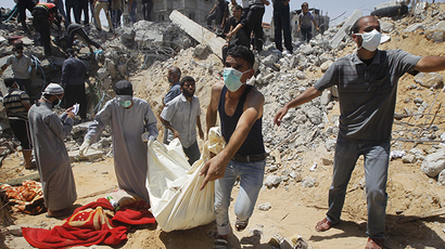 Palestinian rescue workers carry the body of a member of the Duheir family after removing it from under the rubble of their home which was destroyed in an Israeli air strike the previous day in Rafah in the southern Gaza Strip (AFP Photo / Said Khadib)