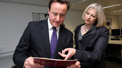 ARCHIVE PHOTO: Britain's Prime Minister David Cameron and Home Secretary Theresa May look at passports during a visit to UK Border Agency staff, in Terminal 5 at Heathrow Airport, London November 23, 2010 (Reuters / Steve Parsons)