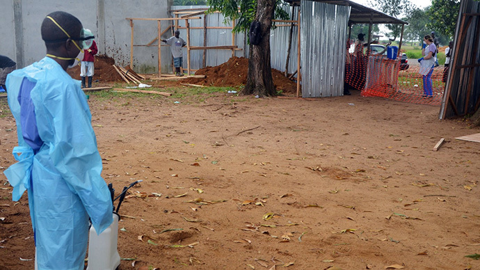Staff member of the Christian charity Samaritan's Purse carrying a spray gun as he treats the area at the entrance of the ELWA hospital in the Liberian capital Monrovia. (AFP Photo / Zoom Dosso)