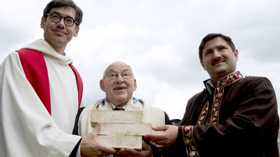 (From L) Pastor Gregor Hohberg, Rabbi Tovia Ben-Chorin and Imam Kadir Sanci hold three bricks as they pose for photographers in the vacant lot where they hope to build a multifaith prayer building, in Berlin (AFP Photo / John Macdougall)