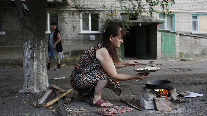 A woman cooks over a campfire due to gas cuts in her building on August 3, 2014 in eastern Ukrainian city of Popasna, Lugansk region (AFP Photo / Anatoly Stepanov)