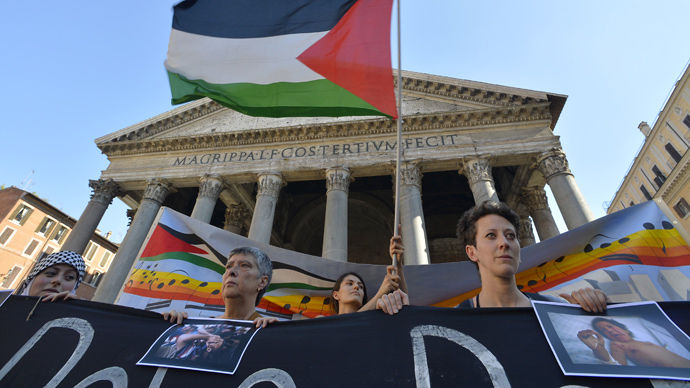 People hold a banner in solidarity with Palestinian people during a protest at the Pantheon in Rome. (AFP Photo / Andreas Solaro)