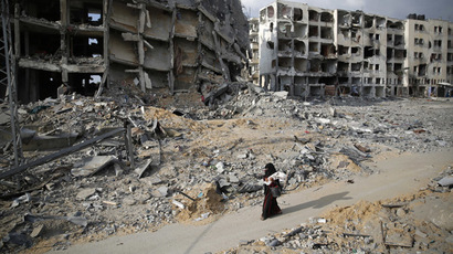 A Palestinian woman walks past buildings destroyed by what police said were Israeli air strikes and shelling in the town of Beit Lahiya in the northern Gaza Strip August 3, 2014. (Reuters/Finbarr O'Reilly)