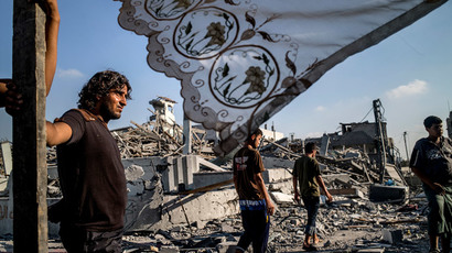Palestinians stand next to a makeshift shelter erected outside their destroyed house in the devastated neighbourhood of Shejaiya in Gaza City on August 6, 2014.(AFP Photo / Marco Longari)