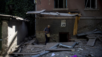 A man going down to the basement of a building damaged during an artillery attack by the Ukrainian Security Forces in Lugansk.(RIA Novosti / Valeriy Melnikov)