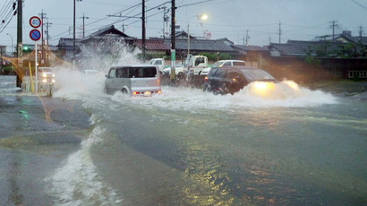 Vehicles drive down a flooded road in the city of Tsu, Mie prefecture as Typhoon Halong brings rain on August 9, 2014. (AFP Photo/Jiji Press)