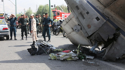 Iranian Revolutionary Guards and security forces stand next to the remains of a plane as they secure the scene of a crash near Tehran's Mehrabad airport on August 10, 2014. (AFP Photo / Atta Kenare)