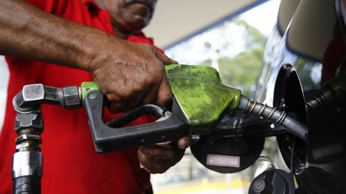 A man pumps gasoline at a service station in Caracas August 7, 2014. (Reuters/Jorge Silva)