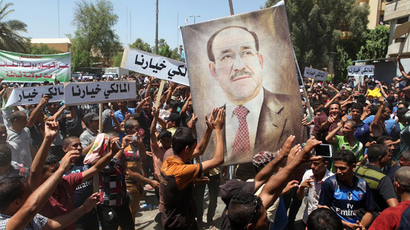 "Iraqis hold placards reading in Arabic ""Maliki is our choice"" during a demonstration to support Iraq's prime minister on August 11, 2014 in Baghdad's central Saadoun Street after Nuri al-Maliki said he was filing a complaint against the president for violating the constitution. (AFP Photo / Amer Al-Saedi)"