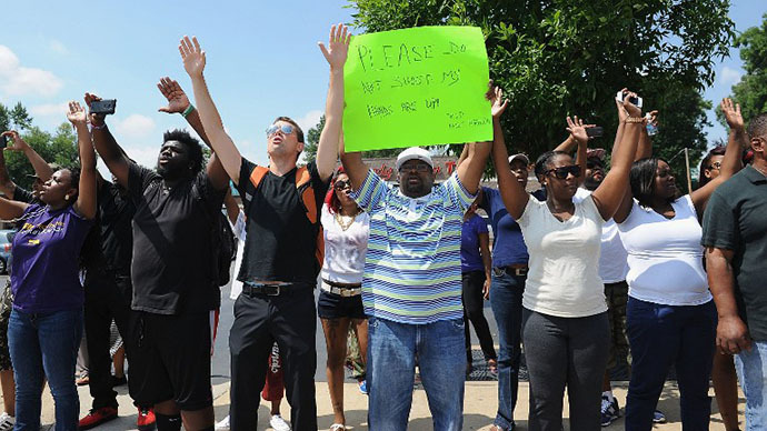 Protestors stand with arms in the air during a protest of the shooting death of 18-year-old Michael Brown by a Ferguson police officer, outside Ferguson Police Department Headquarters August 11, 2014 in Ferguson, Missouri. (AFP Photo / Getty Images / Michael B. Thomas)