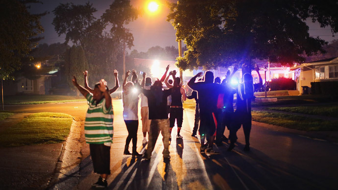 With their hands raised, residents gather at a police line as the neighborhood is locked down following skirmishes on August 11, 2014 in Ferguson, Missouri.  (Scott Olson / Getty Images / AFP)
