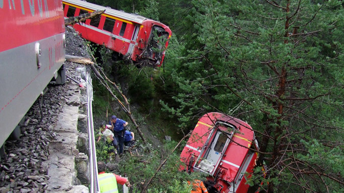 This handout picture taken and released by the police of the Canton of Graubuenden on August 13, 2014 shows rescuers working near a train after it was derailed by a landslide near Tiefencastel, in a mountainous part of eastern Switzerland, on August 13, 1014. (AFP Photo)
