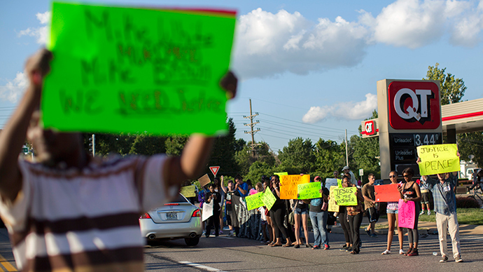 Demonstrators hold signs while protesting the death of black teenager Michael Brown in Ferguson, Missouri August 12, 2014 (Reuters / Mario Anzuoni)