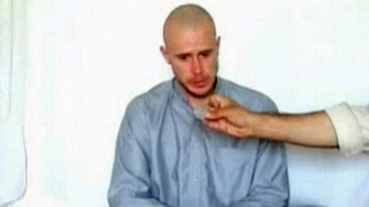 U.S. Army Private Bowe Bergdahl watches as one of his captors displays his identity tag to the camera at an unknown location in Afghanistan, July 19, 2009. (Reuters)