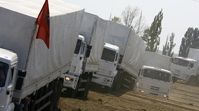 Trucks from a Russian humanitarian convoy arrive to park on a field outside the town of Kamensk-Shakhtinsky in the Rostov region, some 30kms from the Russian-Ukrainian border, Russia, on August 14, 2014. (AFP Photo / Andrey Kronberg)