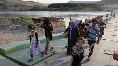 Displaced people from the minority Yazidi sect, fleeing the violence in the Iraqi town of Sinjar, re-enter Iraq from Syria at the Iraqi-Syrian border crossing in Fishkhabour, Dohuk province, August 14, 2014. (Reuters / Youssef Boudlal)
