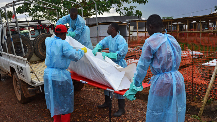 Sierra Leone government burial team members load the body of an Ebola victim onto a truck at an MSF facility in Kailahun, on August 14, 2014. (AFP Photo / Carl de Souza)