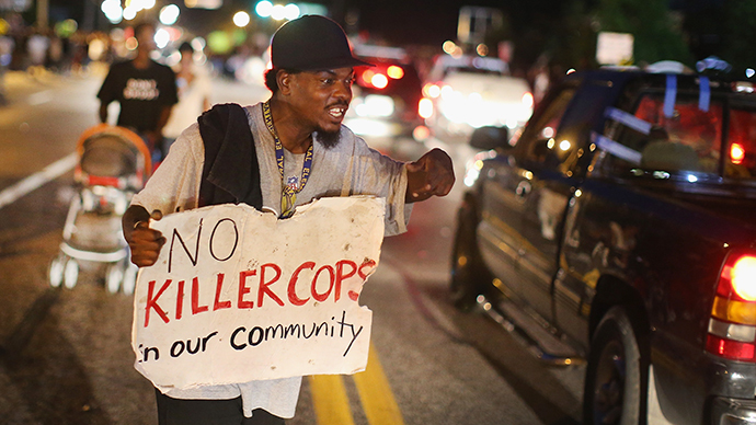 A demonstrator holds a sign along West Florissant Avenue to protest the shooting death of Michael Brown on August 14, 2014 in Ferguson, Missouri. (AFP Photo / Getty Images / Scott Olson)