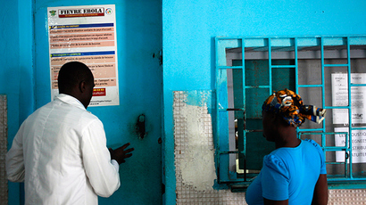 A woman stands at a pharmacy next to a poster displaying a government message against Ebola, at a maternity hospital in Abidjan August 14, 2014 (Reuters / Luc Gnago)