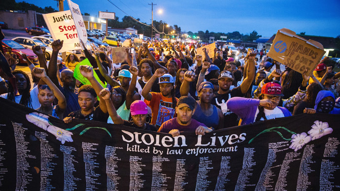 Protestors march and hold their fists aloft as they march during ongoing demonstrations in reaction to the shooting of Michael Brown in Ferguson, Missouri August 16, 2014. (Reuters/Lucas Jackson)