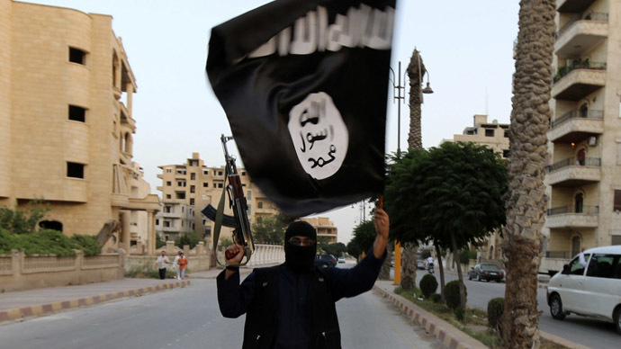 A member loyal to the Islamic State in Iraq and the Levant (ISIL) waves an ISIL flag in Raqqa June 29, 2014. (Reuters)