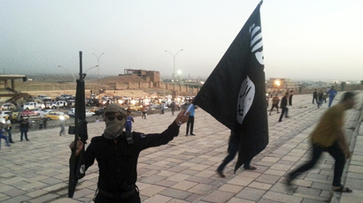 A fighter of the Islamic State of Iraq and the Levant (ISIL) holds an ISIL flag and a weapon on a street in the city of Mosul, June 23, 2014. (Reuters)