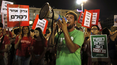 "Demonstrators hold up placards reading in Hebrew: ""One justice for all"" (L) and ""when there is no peace war comes (R)"" as thousands of Israelis protest during a left-wing peace rally in the coastal city of Tel Aviv calling for the Israeli government to negotiate with the Palestinian Authority on August 16, 2014. (AFP Photo / Gali Tibbon)"