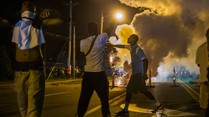 Protesters involved with a more vocal and confrontational group of demonstrators stand and gesture as tear gas is fired, at further protests in reaction to the shooting of Michael Brown near Ferguson, Missouri August 18, 2014. (Reuters / Lucas Jackson)