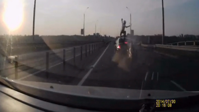 Biker survives rear-ending car by vaulting on to its roof (VIDEO)