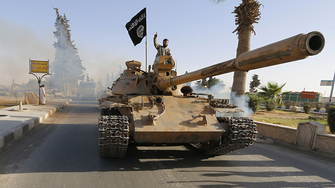 Militant Islamist fighters on a tank take part in a military parade along the streets of northern Raqqa province (Reuters)