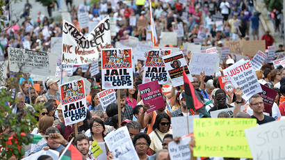 Protesters at a rally against police brutality in memory of Eric Garner August 23, 2014 in Staten Island, New York. The New York City medical examiner's office ruled that Garner, the 43-year-old father of six, died from a chokehold and chest compressions while being arrested by the police on July 17, 2014 (AFP Photo / Stan Honda)