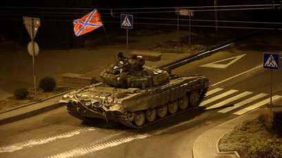 A tank with a flag of Novorossia (union of Donetsk people's republic and Lugansk people's republic) drives in central Donetsk late on August 23, 2014. (AFP Photo / Max Vetrov)
