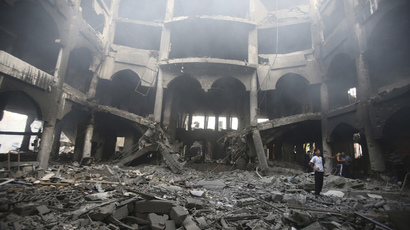 A Palestinian looks at the remains of a commercial center, which witnesses said was hit by an Israeli air strike on Saturday, in Rafah in the southern Gaza Strip August 24, 2014. (Reuters / Ibraheem Abu Mustafa)