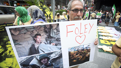 A man holds up a sign in memory of U.S. journalist James Foley during a protest against the Assad regime in Syria in Times Square in New York August 22, 2014. (Reuters / Carlo Allegri)