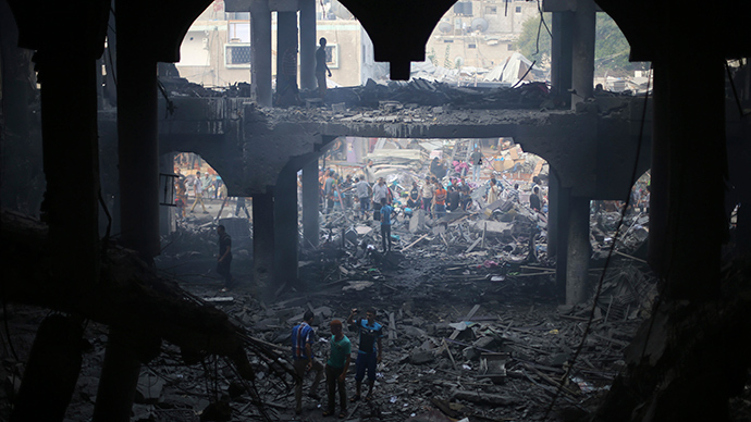 Palestinians look at the remains of a commercial center, which witnesses said was hit by an Israeli air strike on Saturday, in Rafah in the southern Gaza Strip August 24, 2014 (Reuters / Ibraheem Abu Mustafa)