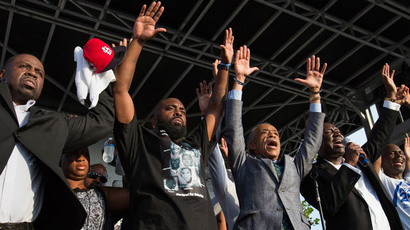 "Lesley McSpadden (2nd L) and Michael Brown Sr. (C), parents of 18-year-old Michael Brown, raise their hands with Reverend Al Sharpton as attorney Benjamin Crump (2nd R) leads the slogan, ""Hands Up, Don't Shoot,"" while attending the Peace Fest 2014 rally in St. Louis, Missouri August 24, 2014.(Reuters / Adrees Latif)"