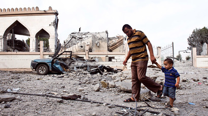A Palestinian man walks with a child past the rubble of a mosque that was partially damaged by an Israeli airstrike on August 25, 2014 in Beit Lahia in the northern Gaza Strip.(AFP Photo / Roberto Schmidt)