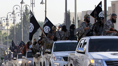 Militant Islamist fighters parade on military vehicles along the streets of northern Raqqa province (Reuters)