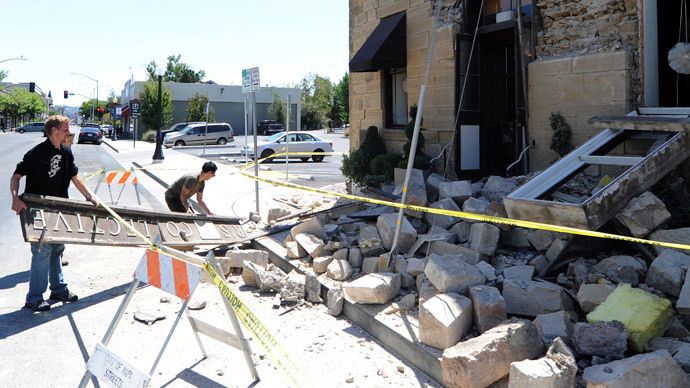 Shop employee's remove a sign from the damaged Alexandria Square building after an early morning earthquake struck Napa, California August 24, 2014.(AFP Photo / Josh Edelson)
