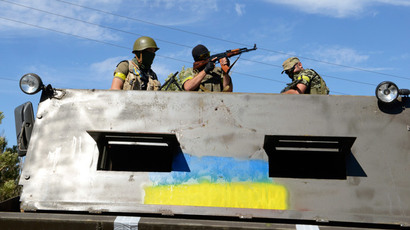 Members of Ukrainian volunteer battalion Dnipro stand in a truck covered in steel plates near the small southern Ukrainian city of Novoazovsk, Donetsk region, on August 27, 2014.(AFP Photo / Alexander Khudoteply)