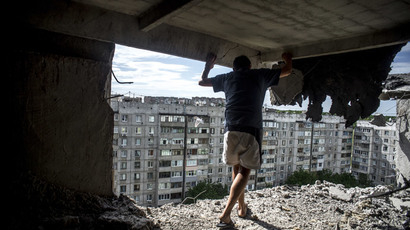 Man inspects damaged residential building in the Mirny district of Lugansk, hit by artillery fire.(RIA Novosti / Valeriy Melnikov)